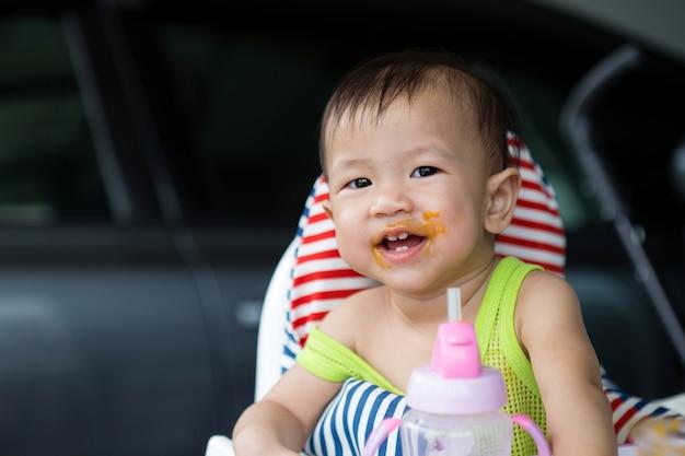 Bebê asiático que come o alimento na cadeira alta, idade de 8 meses