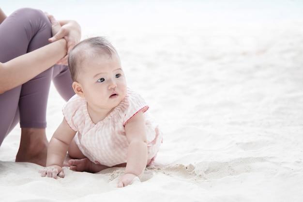 Bebê asiático rastejando na areia perto da mãe