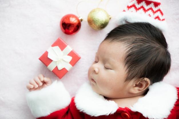 Bebê asiático recém-nascido em uniforme de papai noel dormindo com presente de caixa vermelha e chapéu vermelho