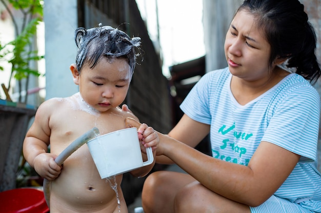 Bebê asiático tomar banho ao ar livre com a mãe.