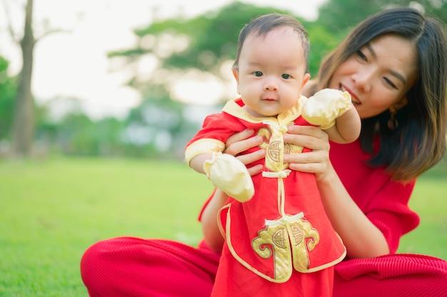 Bebê asiático vestindo um terno vermelho chinês com a mãe