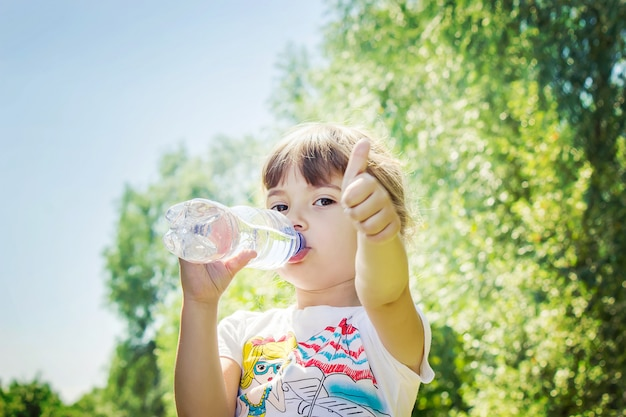 Bebê bebe água da garrafa. foco seletivo.