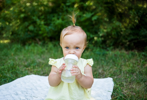 Bebê bebe água de mamadeira na natureza