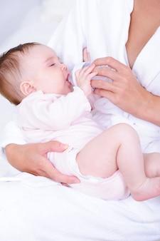 Bebê bebendo leite da mamadeira pela enfermeira