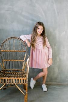 Bebê bonito 5-6 anos de idade usando vestido elegante rosa overgrey fundo. olhando para a câmera. festa de aniversário. celebração.