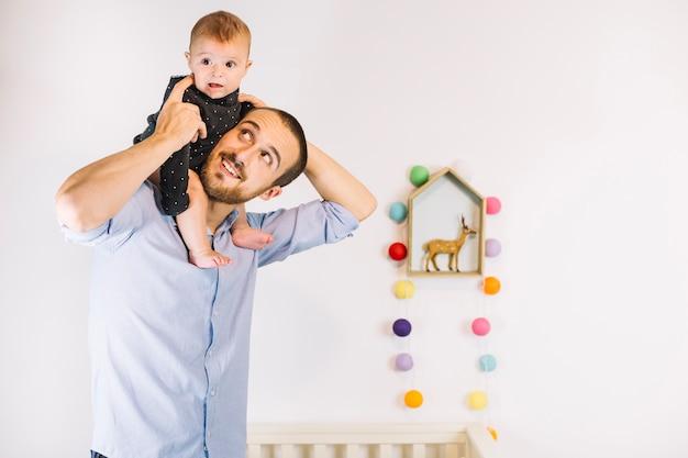 Bebê bonito andando nos ombros do pai