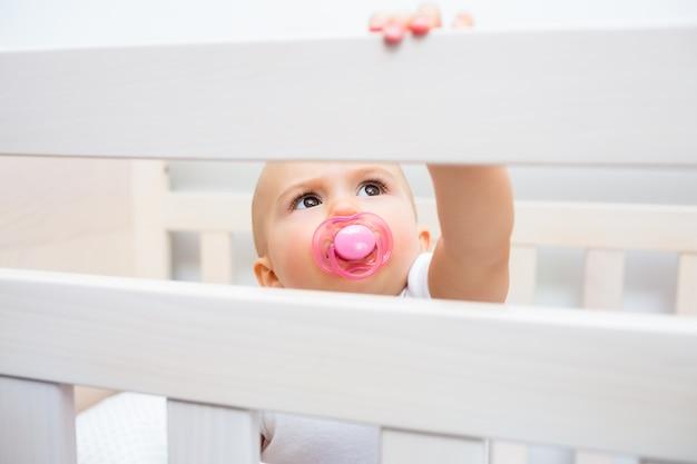 Bebê bonito com chupeta na boca no berço