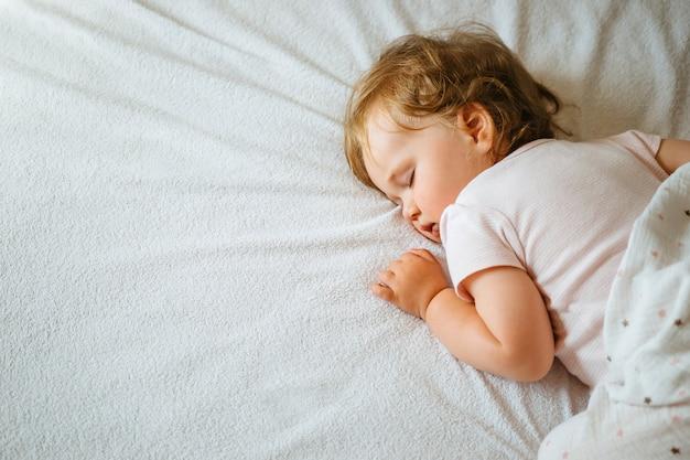 Bebê bonito da criança que dorme em sua barriga nos lençóis brancos, espaço livre.