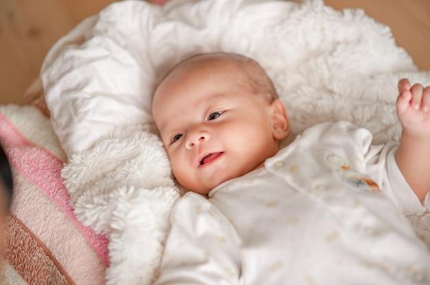 Bebé bonito em um quarto da luz branca o bebê recém-nascido é bonito. na cama para crianças nascidas - imagens