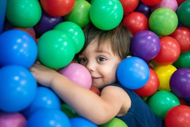 Bebê bonito menino criança - na piscina de bolas
