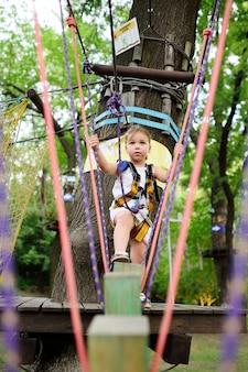 Bebé bonito na engrenagem de escalada em um parque da corda