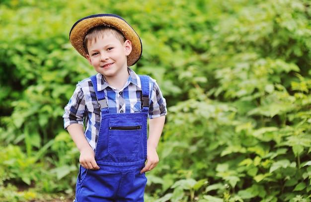 Bebé bonito pequeno no chapéu de palha, na camisa de manta e no jumpsuit azul do trabalho no fundo verde.