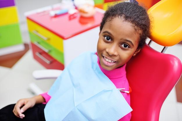 Bebé bonito preto sorrindo sentado em uma cadeira odontológica vermelha