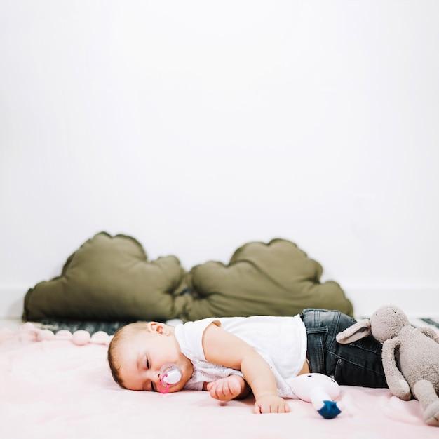 Bebê bonito que dorme pacificamente no chão do berçário