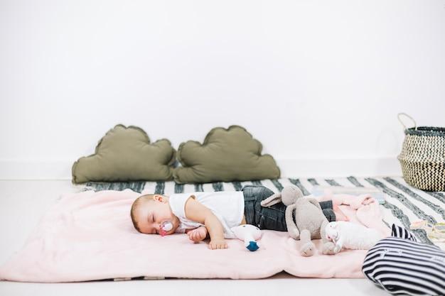 Bebê bonito que dorme pacificamente no cobertor rosa