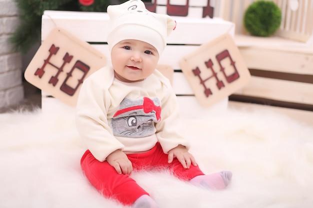 Bebé bonito que senta-se sob a árvore de natal na sala