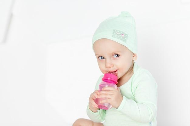 Bebé brinca com brinquedos no quarto das crianças em casa com fato verde, o conceito de desenvolvimento e lazer das crianças pequenas
