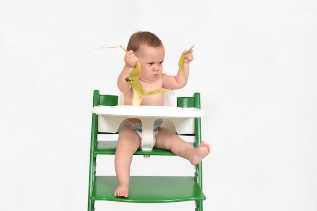 Bebê brincando com banana no fundo branco