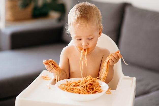 Bebê brincando com macarrão em sua cadeira alta