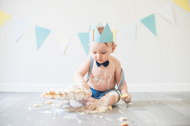 Bebê brincando com um bolo durante a sua festa de aniversário do bolo smash