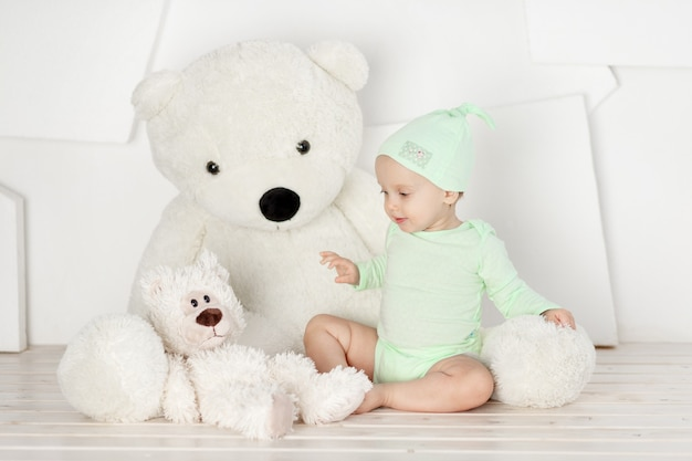 Bebê brincando com um grande ursinho de pelúcia em casa em um quarto bem iluminado, brincadeira infantil e conceito de lazer