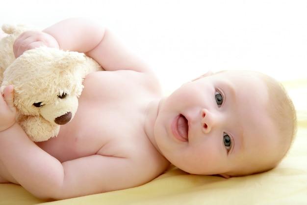 Bebê brincando de ursinho deitado na cama