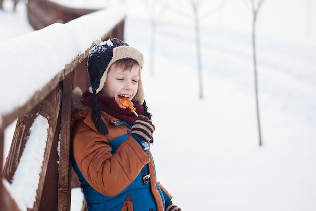 Bebê brincando e comendo galo doce em dia de inverno. as crianças brincam no bosque nevado.