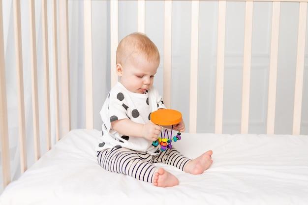 Bebê brincando no berço, desenvolvimento inicial de crianças até um ano