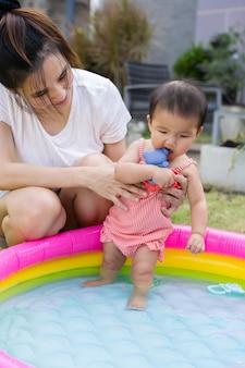 Bebê carregado pela mãe desfrutando da piscina inflável