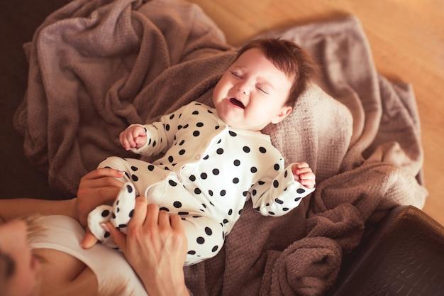 Bebê chorando nas mãos da mãe com dor de estômago