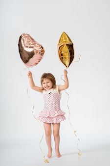 Bebê com balões em forma de coração e estrelas