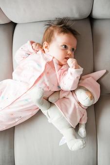 Bebê com brinquedo deitado no sofá em casa