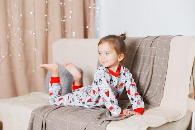 Bebê com cabelo loiro no básico de pijama de papai noel no sofá e sonhando acordado ano novo natal