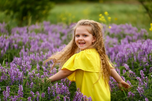 Bebê com cachos girando em um campo de lavanda, vestido com um vestido amarelo, noite de verão