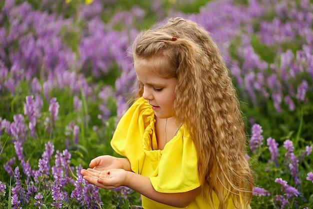 Bebê com cachos sentado no campo, segurando uma joaninha, vestida com um vestido amarelo, noite de verão
