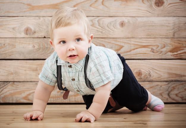 Bebê com camiseta e shorts suspensórios na mesa de madeira