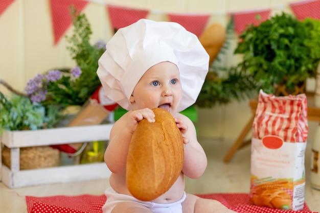 Bebê com chapéu de cozinheiro e comida ao redor