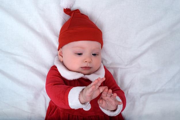 Bebê com chapéu de papai noel, deitado sobre um fundo branco, brinca com as mãos. conceito de natal