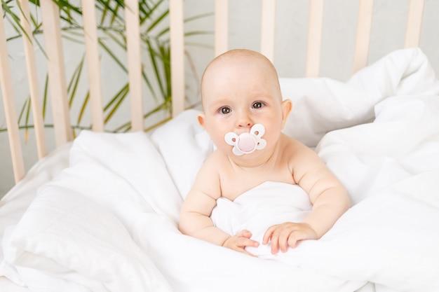 Bebé com chupeta num berço numa cama de algodão branco com seis meses de idade
