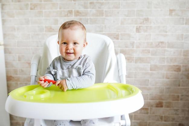 Bebê com colher na cadeira na sala de jantar, sorrindo e feliz criança.