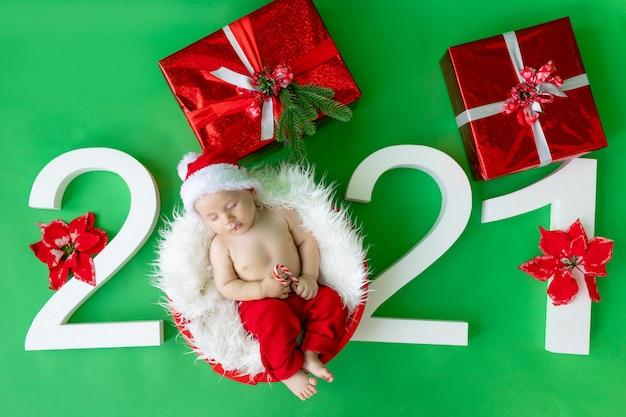 Bebê com fantasia de papai noel deitado sobre um fundo verde