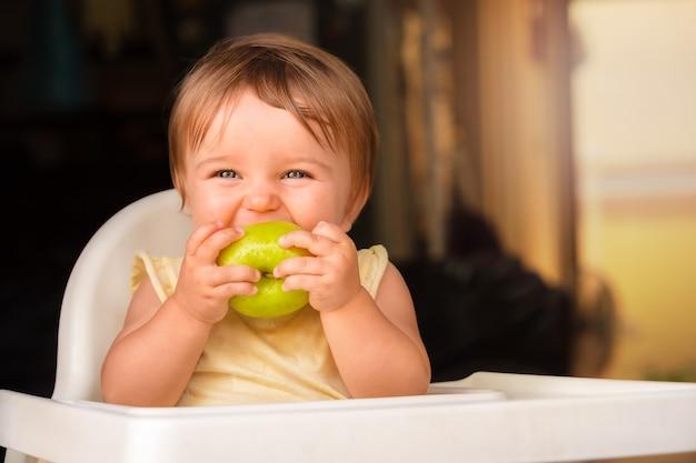 Bebê com maçã verde. criança morde uma maçã e ri