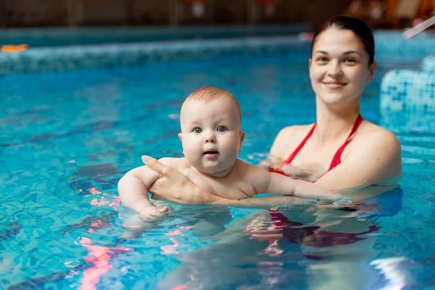Bebê com mãe aprende a nadar na piscina