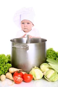 Bebê com o chef do chapéu cercado por legumes