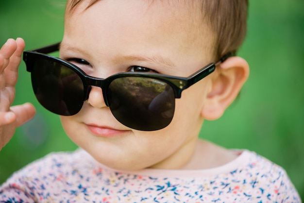 Bebê com óculos de sol na relva verde
