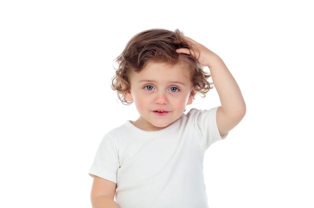 Bebê com olhos azuis tocando a cabeça dele