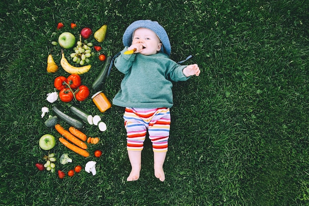 Bebê com roupas coloridas, experimentando comida e moldura de diferentes frutas frescas vegetais na grama verde