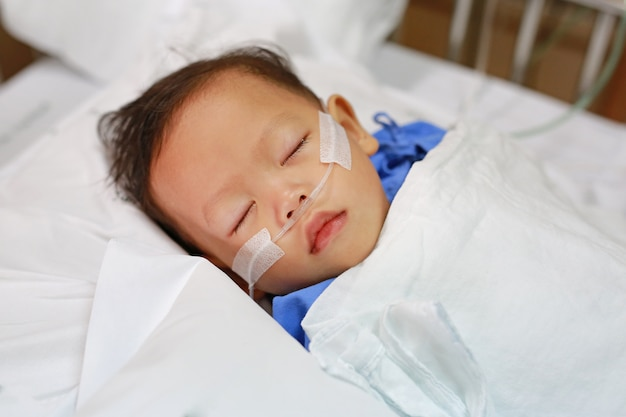 Bebé com tubo de respiração no nariz que recebe o tratamento médico. cuidados intensivos no hospital.