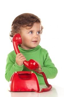 Bebê com um ano de idade brincando com um telefone vermelho