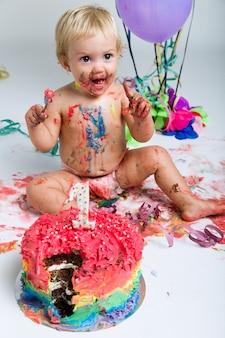 Bebé comemorando seu primeiro bithday com bolo gourmet e ba